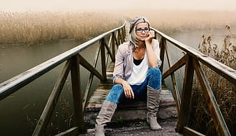 Woman in white shirt with brown cardigan and brown boots sitting on brown wooden bridge during daytime