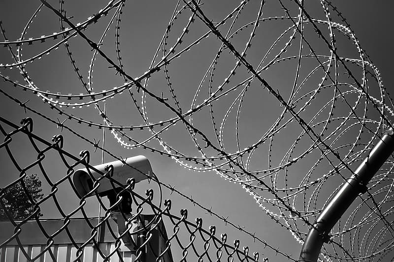 Grayscale photo of CCTV camera near bulb wire fence