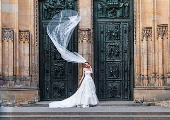 Woman wearing wedding dress standing in front of brown and black building while wedding veil's floating on midair