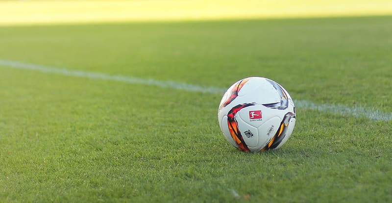 White and black soccer ball on field