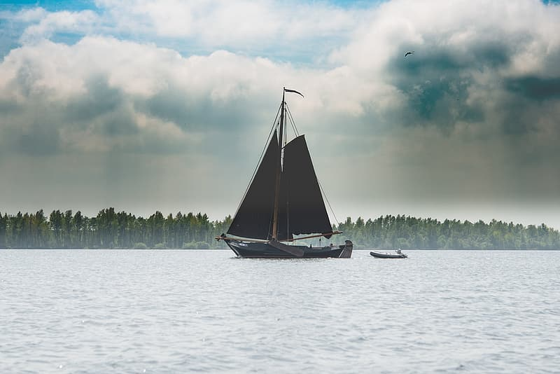Boat sailing on body of water under cloudy daytime