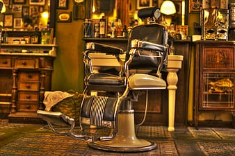 White and black leather barber chair on green floor mat