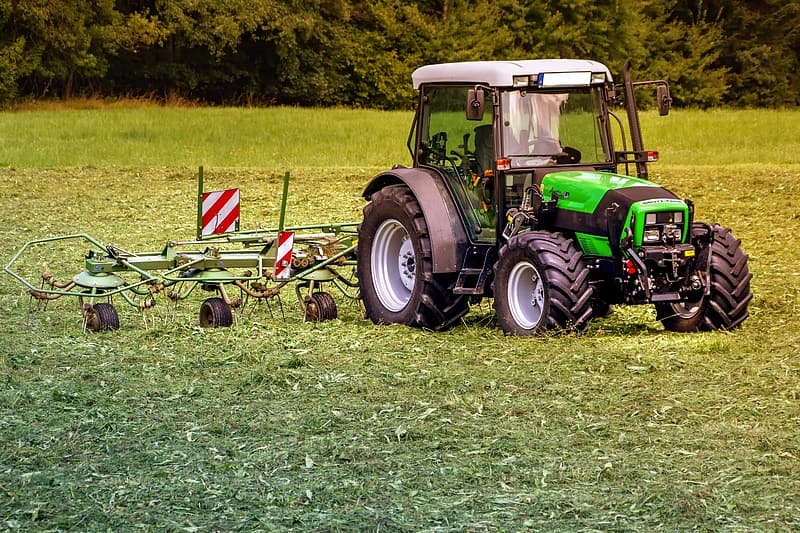 Green and yellow tractor on green grass field during daytime