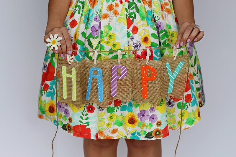 Person wearing yellow and red floral dress holding happy text printed hanging decor