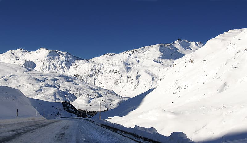 Snow covered concrete road between snow covered mountains at daytime
