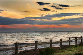 Brown wooden fence on sea during sunset