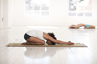 Woman in white tank top and black shorts doing yoga in brown yoga mat