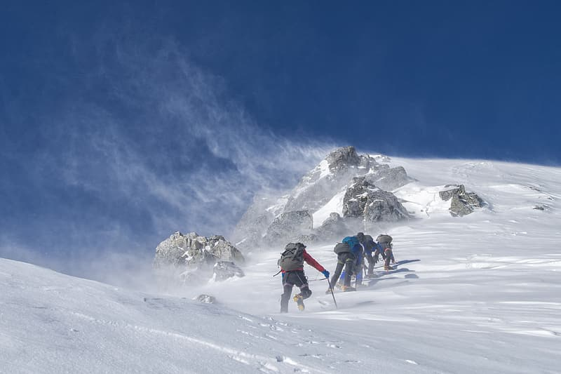 Group of people climbing mountain covered in snow at daytime
