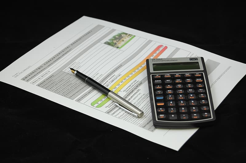 Black and gray desk calculator with pen