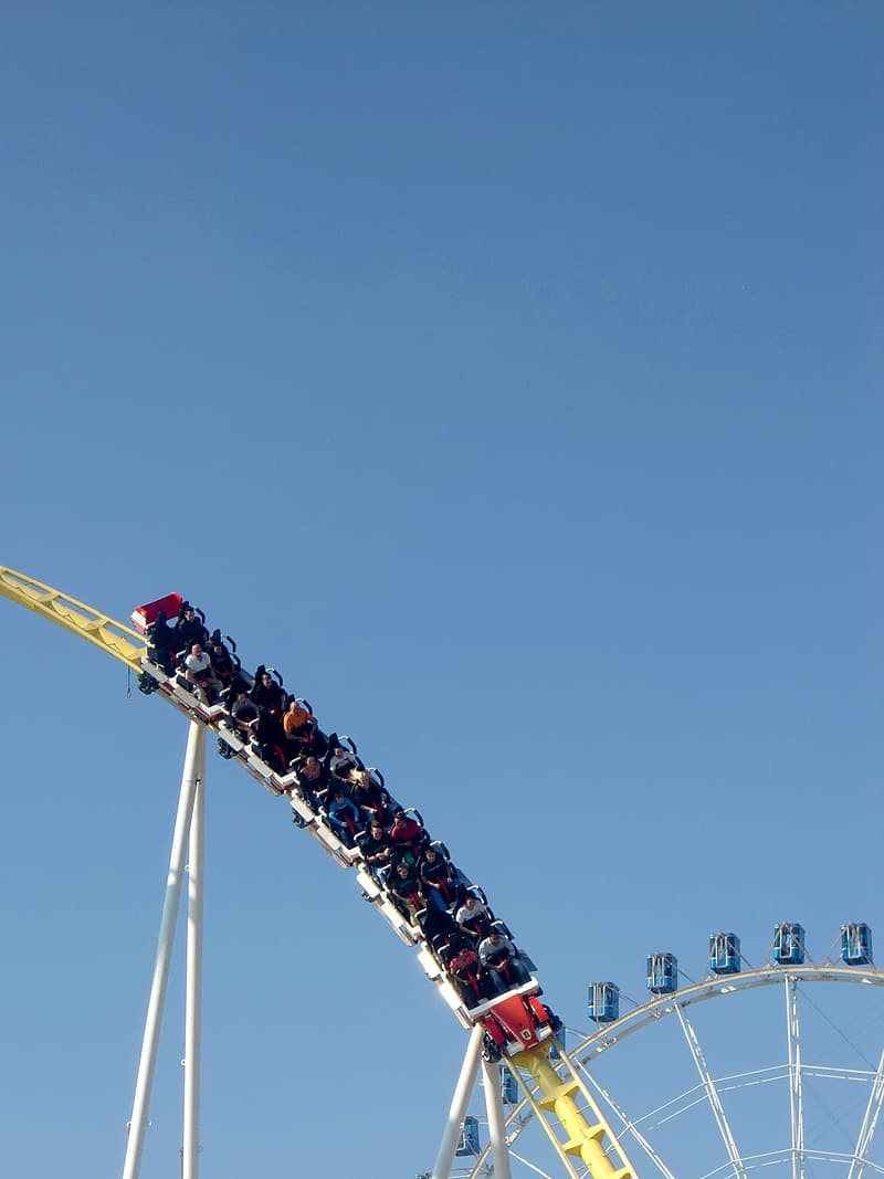 People riding roller coaster during daytime