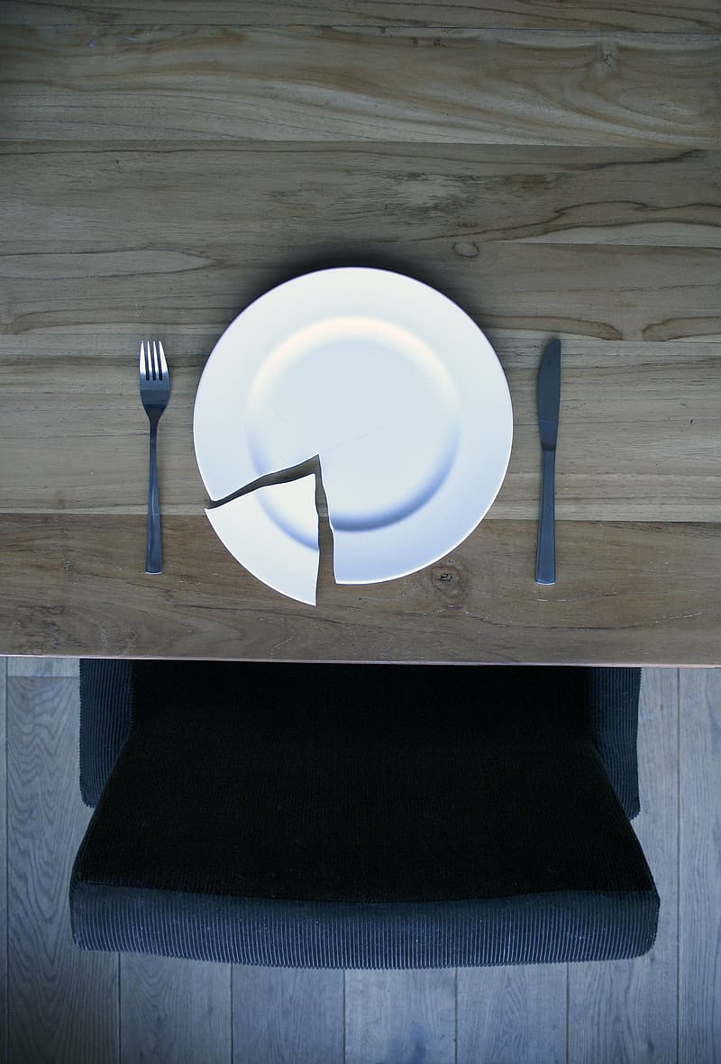 Broken round white ceramic plate between gray stainless steel fork and butter spreader