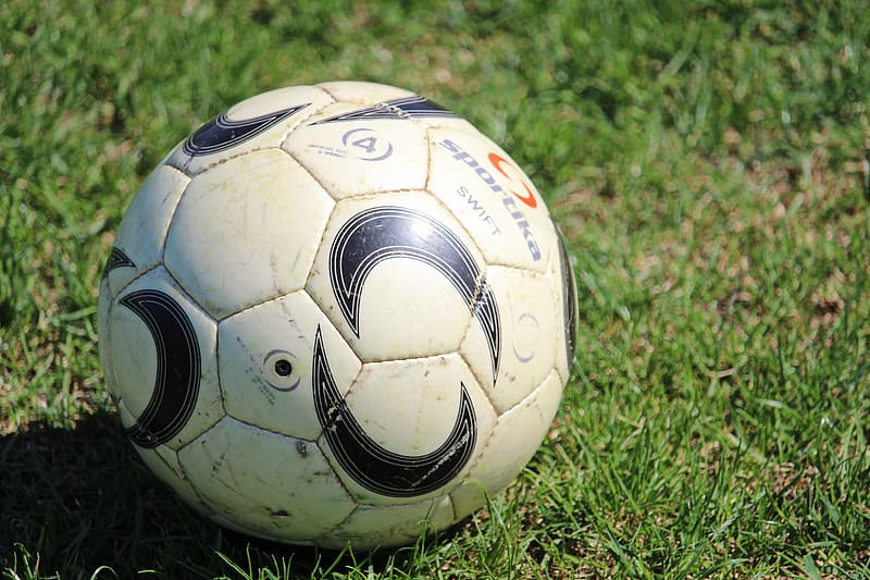 White and black soccer ball on green grass field