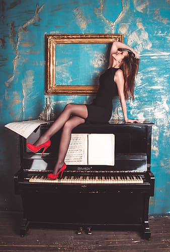 Woman on top of black upright piano