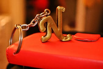 Selective focus photography of gold-colored N key chain