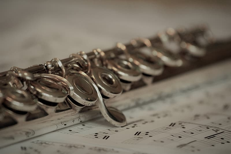 Silver-colored flute on musical sheet