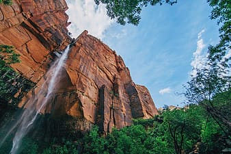 Brown rock formation with green trees under blue sky during daytime