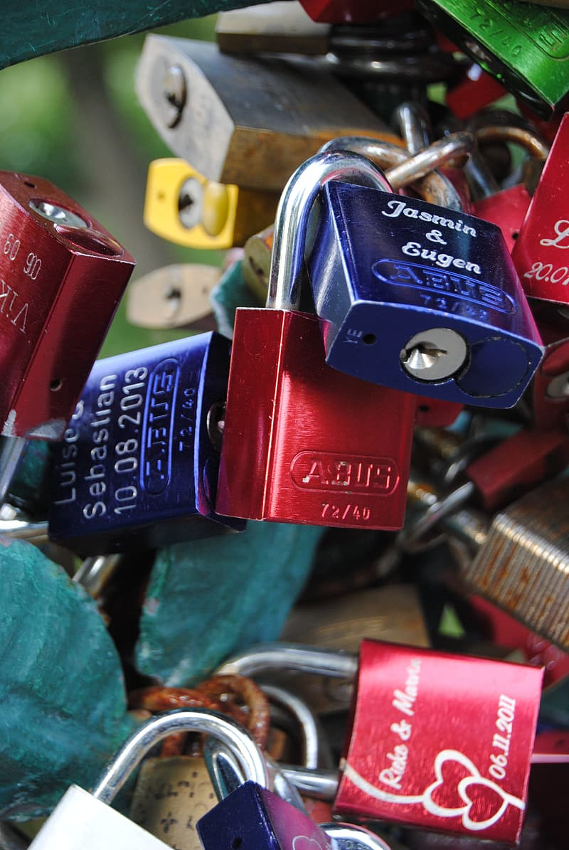 Red and blue padlock on green metal fence