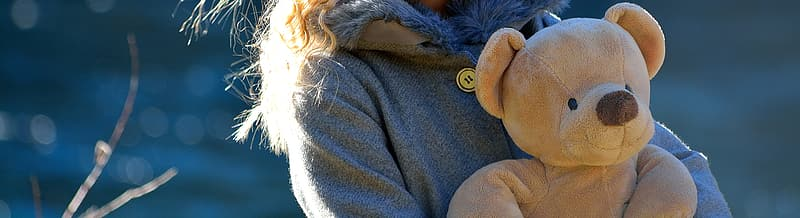 Person holding beige bear plush toy