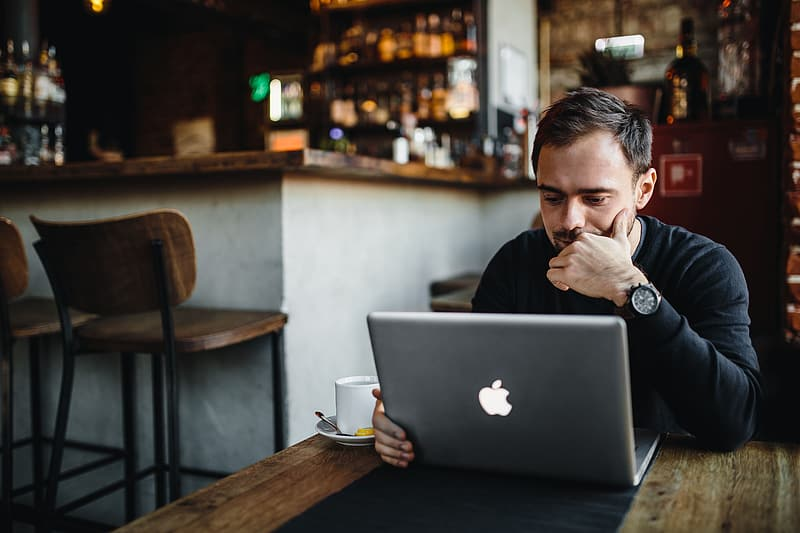 Man in black long sleeve shirt sitting in front of silver macbook