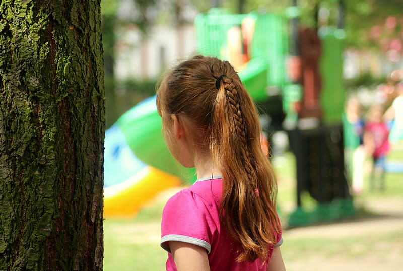 Girl in pink t-shirt standing beside tree during daytime