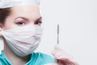 Woman wearing face mask and holding scalpel knife