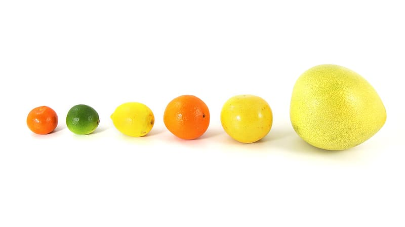 Six assorted-color fruits on white surface