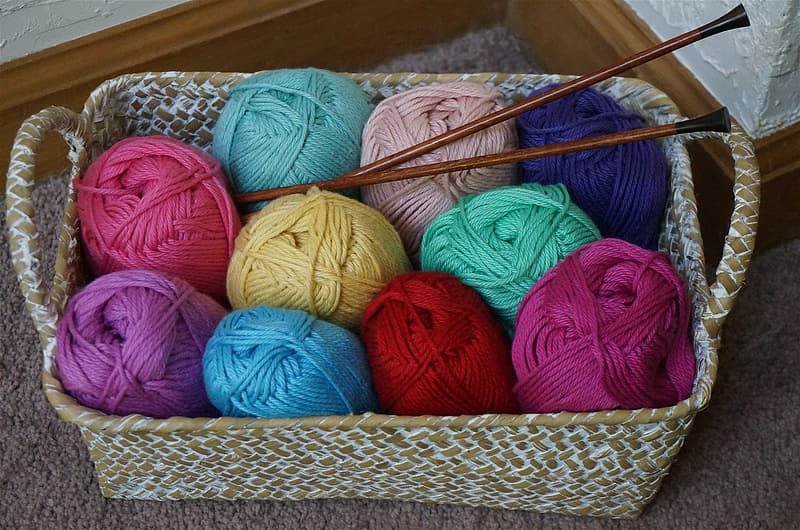 Assorted-color yarn rolls in basket with hooks