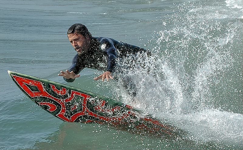 Man in black wet suit riding red surfboard on water waves during daytime