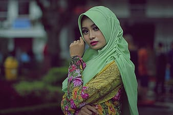 Woman in pink hijab and yellow and green floral dress