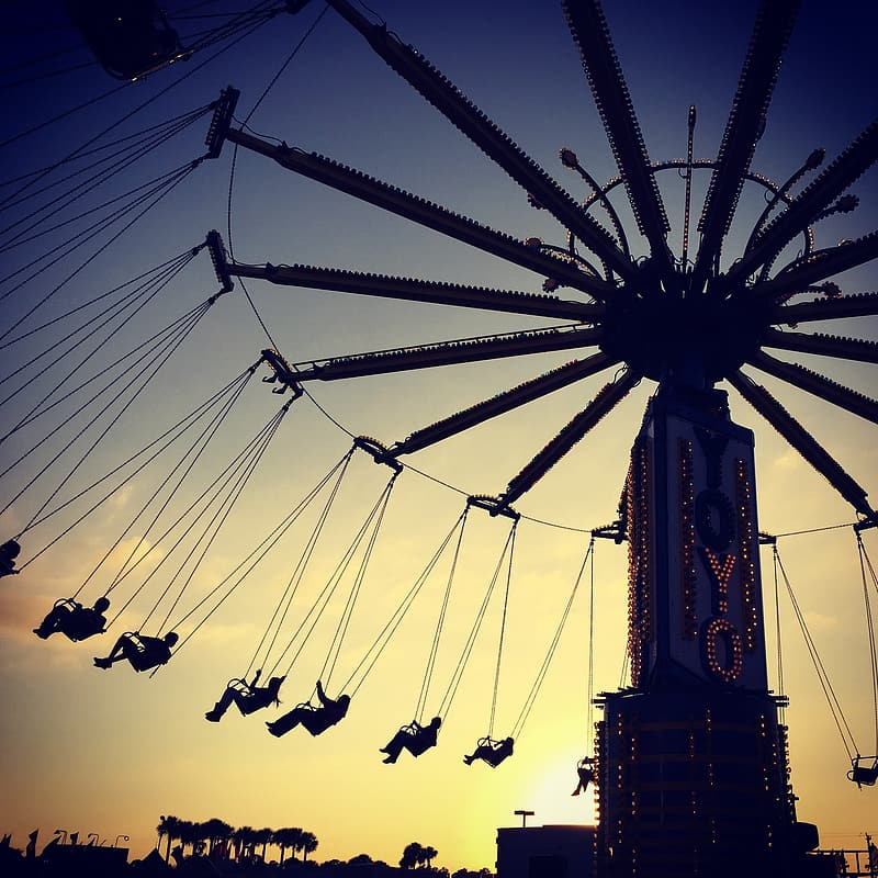 Silhouette of people riding on amusement park ride during sunset
