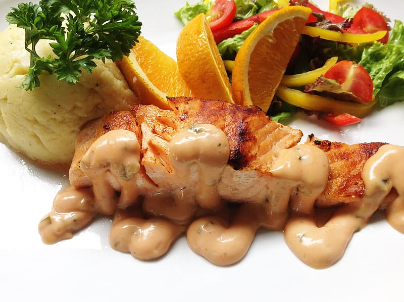 Grilled fish covered in sauce with slices of orange, and mash potat