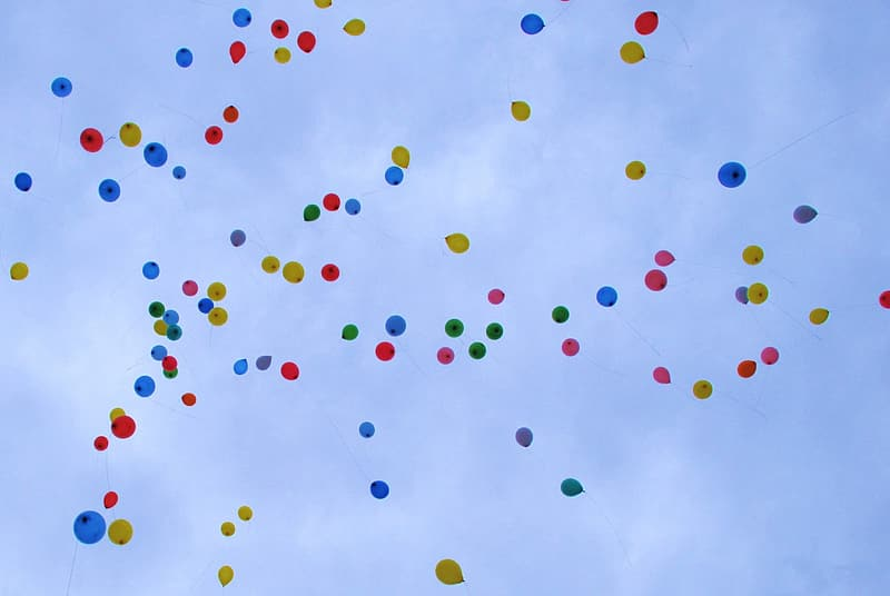 Assorted balloons on mid air under cloudy sky during daytime