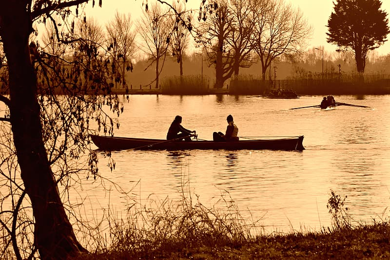 Silhouette of 2 people riding on boat on lake during sunset