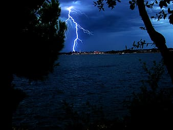 Lightning strikes near high rise building on the other side of the lake