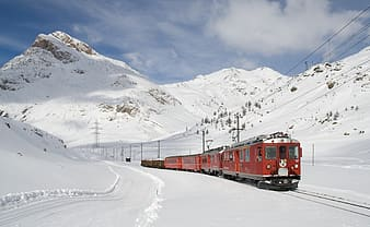 Red train on snow under blue sky