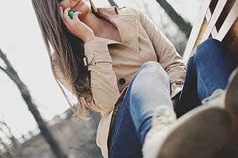 Woman in brown leather jacket and blue denim jeans sitting on brown wooden bench during daytime