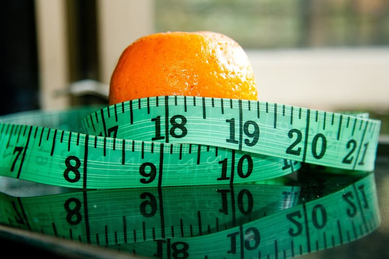 Orange fruit wrapped by tape measure