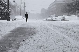 Person in black jacket walking on snow covered road during daytime