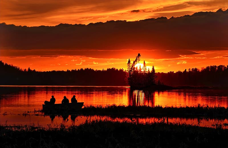 Silhouette of three person on boat during sunset