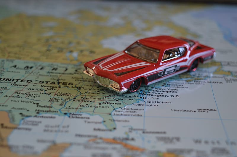 Red muscle car die-cast scale model on map sketch