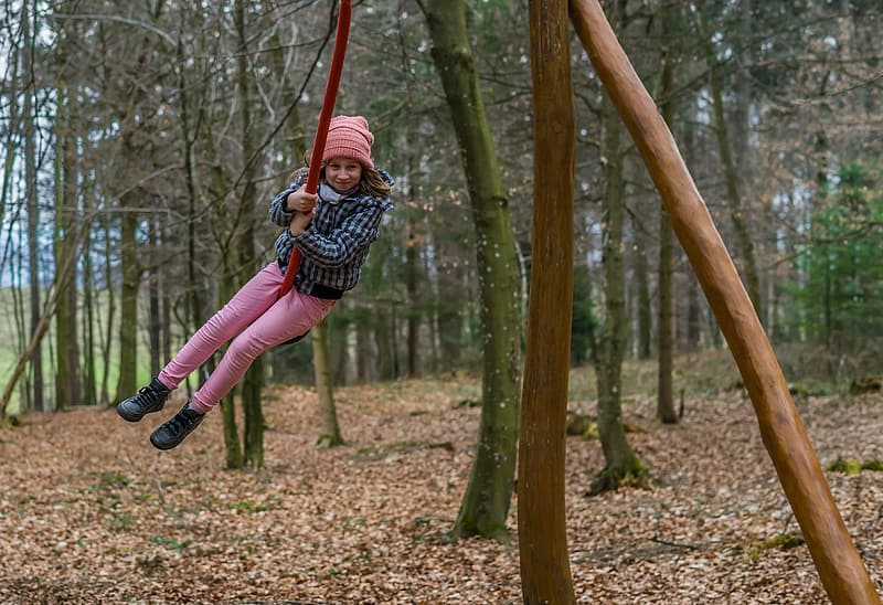 Girl in black and white jacket and pink pants sitting on brown wooden swing during daytime