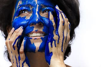 Smiling woman with blue paint on her face
