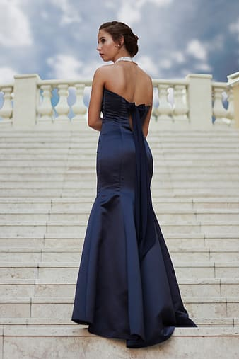 Woman wearing strapless dress standing on stairs
