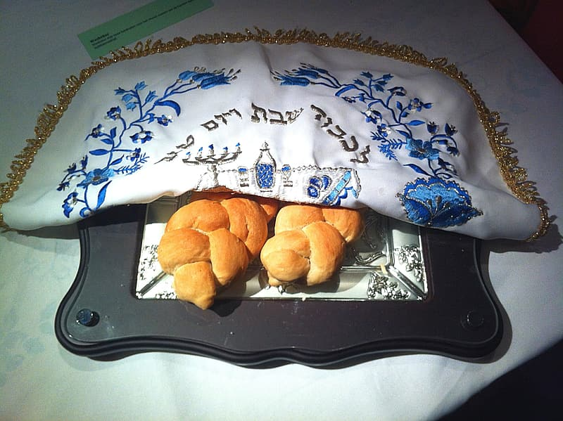 Two breads under a white and blue textile cover
