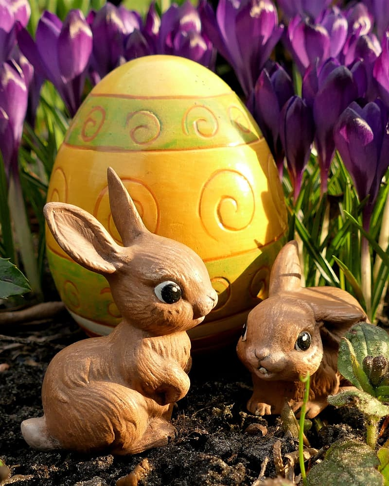 Two rabbit figurines near yellow decorative egg and purple flowers during day