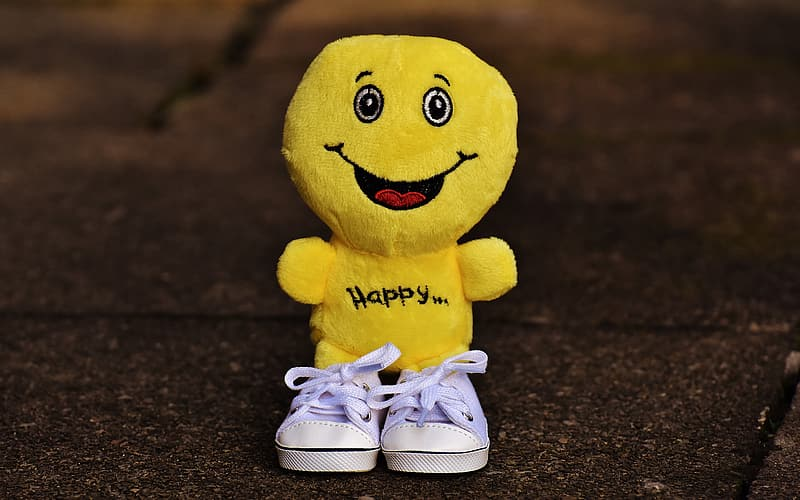 Selective focus photography of happy plush toy with shoes