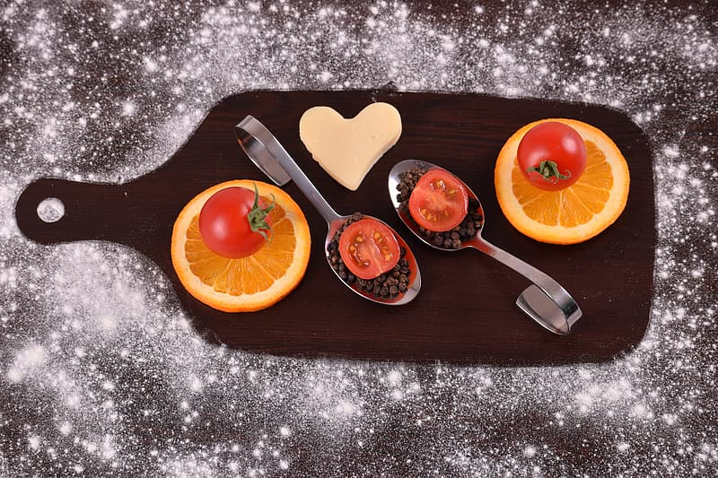 Sliced orange fruit beside stainless steel fork on blue and white floral table cloth