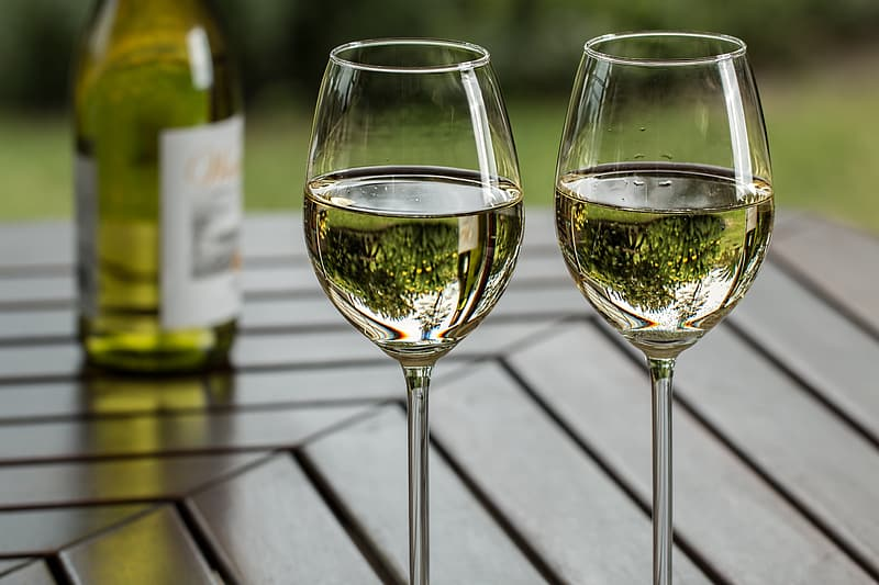Two clear wine glasses on brown wooden table