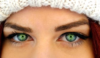 Woman with green eyes wearing white crochet hat
