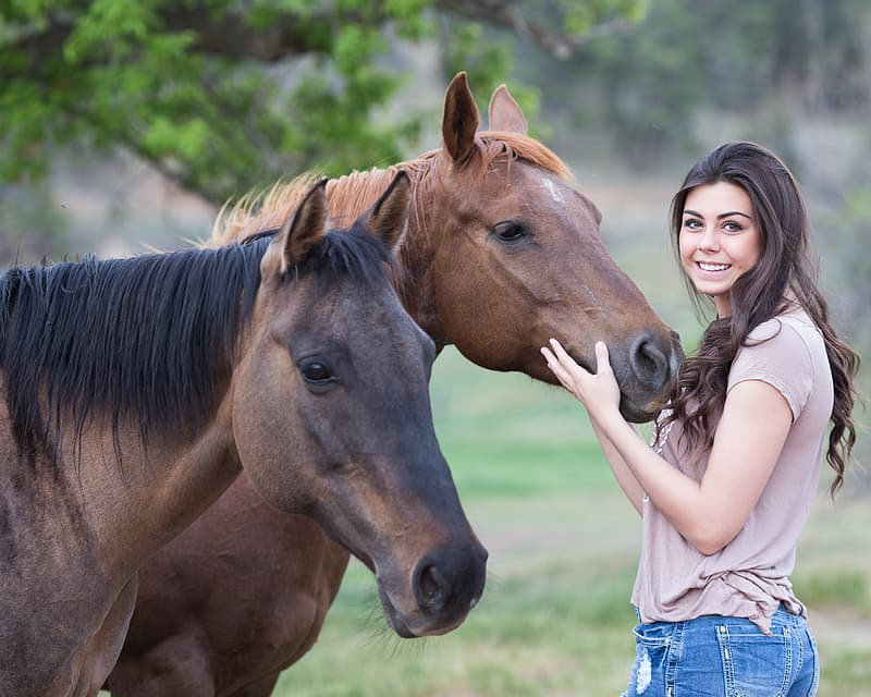 Woman holding head of brown horse on field during daytime